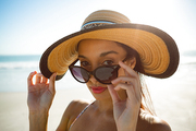 Portrait of beautiful mixed race woman in hat looking over sunglasses on the beach