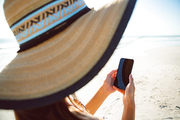 Side view of mixed race woman in hat using mobile phone on beach in the sunshine