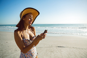 Side view of beautiful mixed race woman in hat using mobile phone on the beach