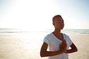 Front view of young African american woman performing yoga on the beach