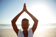Front view of young African-american woman performing yoga on the beach