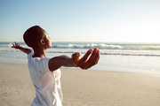 rear view of young African-american woman performing yoga on the beach