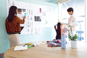 Rear view of beautiful diverse female fashion designers working in a modern office