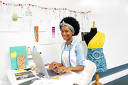 Side view of African american female graphic designer using laptop in office