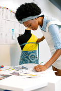 Side view of African american female graphic designer writing on paper while measuring mannequin in office