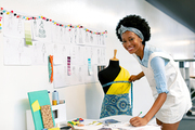 Side view of happy African american female graphic designer writing on paper while measuring mannequin in office
