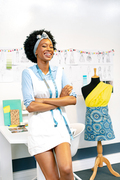 Front view of happy African american female fashion designer with arms crossed looking at camera in office