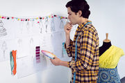 Side view of Caucasian male fashion designer looking at color swatch in office