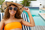 Front view of happy mixed-race woman in bikini relaxing on a sun lounger near swimming pool at the backyard of home. Summer fun at home by the swimming pool