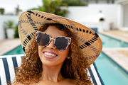 Front view of happy mixed-race woman relaxing on a sun lounger near swimming pool at the backyard of home. Summer fun at home by the swimming pool