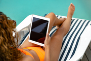 Rear view of Mixed-race woman using digital tablet while relaxing on a sun lounger near swimming pool at the backyard of home. Summer fun at home by the swimming pool