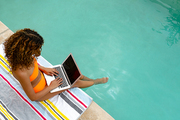 High angle view of mixed-race woman using laptop while sitting at the edge of swimming pool. Summer fun at home by the swimming pool