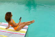 High angle view of beautiful mixed-race woman using mobile phone while sitting at the edge of swimming pool. Summer fun at home by the swimming pool