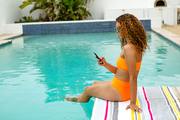Side view of beautiful mixed-race woman using mobile phone while sitting at the edge of swimming pool. Summer fun at home by the swimming pool