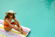 High angle view of beautiful mixed-race woman in sunglasses and hat sitting at the edge of swimming pool. Summer fun at home by the swimming pool
