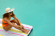 High angle view of thoughtful mixed-race woman in bikini and hat sitting at the edge of swimming pool. Summer fun at home by the swimming pool