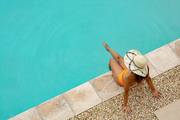 High angle view of mixed-race woman in bikini and hat sitting at the edge of swimming pool. Summer fun at home by the swimming pool