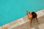 High angle view of mixed-race woman sitting at the edge of swimming pool in the backyard at home. Summer fun at home by the swimming pool