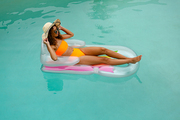 High angle view of mixed-race woman in bikini relaxing on a inflatable tube in swimming pool at the backyard of home. Summer fun at home by the swimming pool