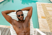 High angle view of handsome shirtless African-american man in sunglasses relaxing on a sun lounger near swimming pool. Summer fun at home by the swimming pool