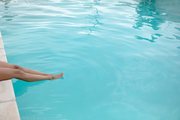 High angle of low section of woman sitting at the edge of swimming pool. Summer fun at home by the swimming pool