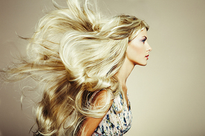 Photo of beautiful woman with magnificent hair. Blonde girl with long and shiny wavy hair . Beautiful model with curly hairstyle