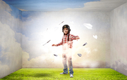 Little cute boy in pilot helmet and paper airplanes flying around