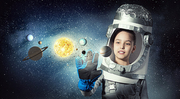 Cute kid girl with carton helmet on head dreaming to become astronaut