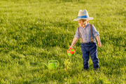 Portrait of toddler child outdoors. Rural scene with one year old baby boy wearing straw hat using watering can