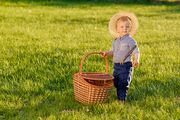 Portrait of toddler child outdoors. Rural scene with one year old baby boy wearing straw hat holding picnic basket