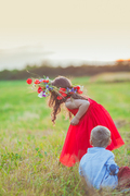 Cute girl is trying to put a floral wreath on her brother head