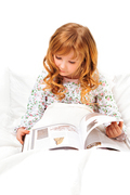 Cute little girl reading before sleep in her bed with white linen