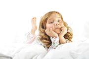 Cute little girl smiling on her with bed