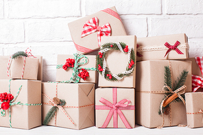 Woman wrapping christmas gifts. Creatively wrapped and decorated christmas presents in boxes on dark wooden background.Top view from above. Flat lay.