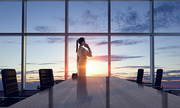 Businesswoman in night office against panoramic window in light of sunset