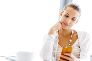 Attractive woman sitting at desk in office holding mobile phone