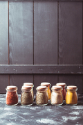 Various grinded spices in vintage glass bottles over wooden wall, copy cpase