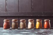 Various grinded spices in vintage glass bottles