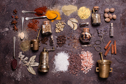 Flat lay composition of various spices and mortars over brown slate background, top view