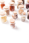 Assortment of dry spices in vintage glass bottles on white background with copy space