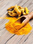 The turmeric spice - powder in a scoop and dry roots on the wooden background