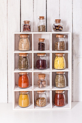 Assortment of dry spices in vintage glass bottles in wooden box