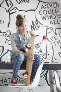 Full-length of girl with skateboard sitting on study table at home