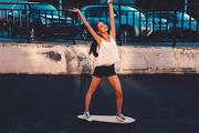 Young woman ride on skateboard in urban setting in happy state celebrate summer freedome with her hands rised outdoors active lifestyle concept