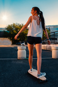 Beautiful girl riding skateboard in short denim shorts, view from back in front of early evening sky