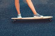 Closeup of skateboarder legs. Woman in sneakers riding skateboard outdoor on asphalt surface. Copyspace on asphalt.