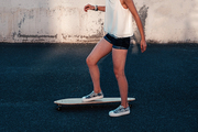 Girl on skateboard in scate park ready to push by her left leg and moving forward, side view shot with copyspace