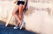 Bare legs of skater girl in short shorts leaning back used wall with her longboard near with her legs crossed a lot of space for text