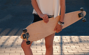 Front view of young girl in shorts holding longboard by both hands. Skateboard Extreme Sport Skater Activity Concept. Shadow pattern on pavement behind model.