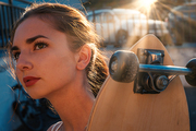Headshot of young girl holding longboard near her face backlit by sunset light shot with sunflares